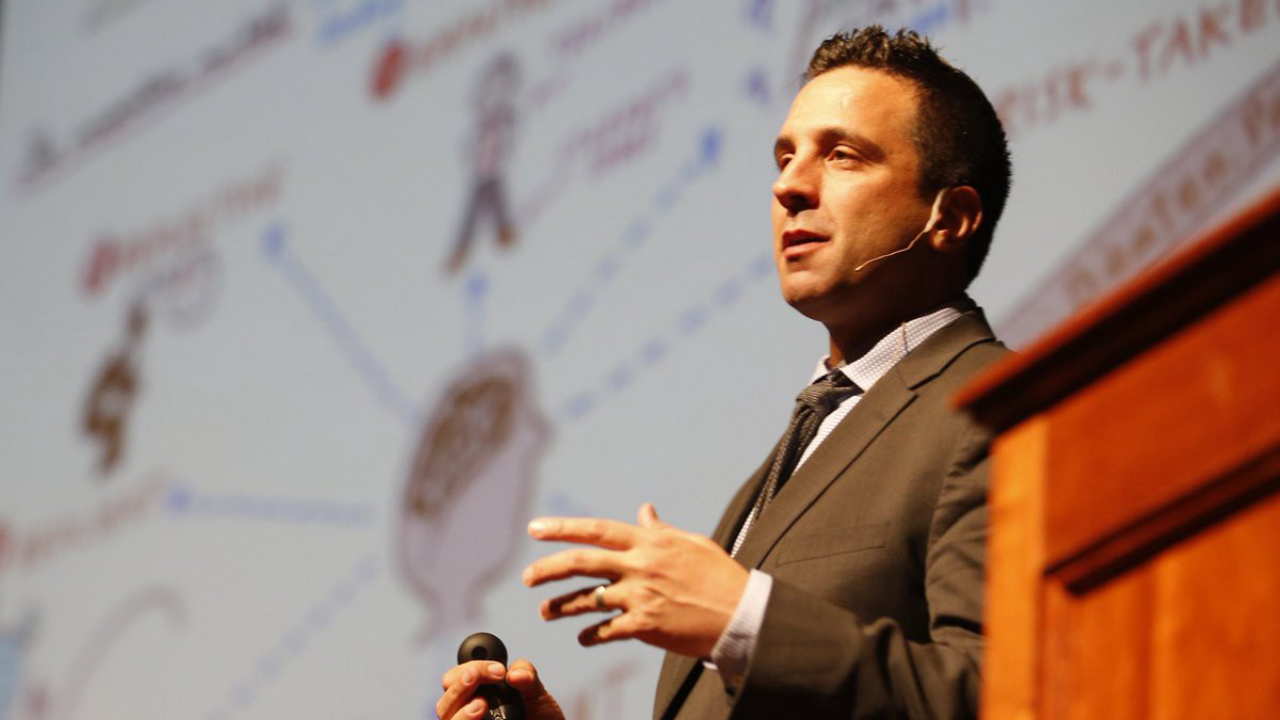George Couros speaking on the stage by a podium